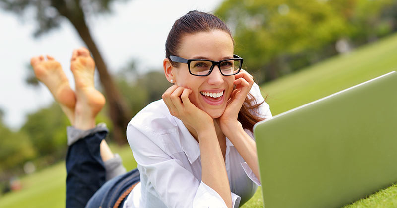 Woman smiling while studying outside